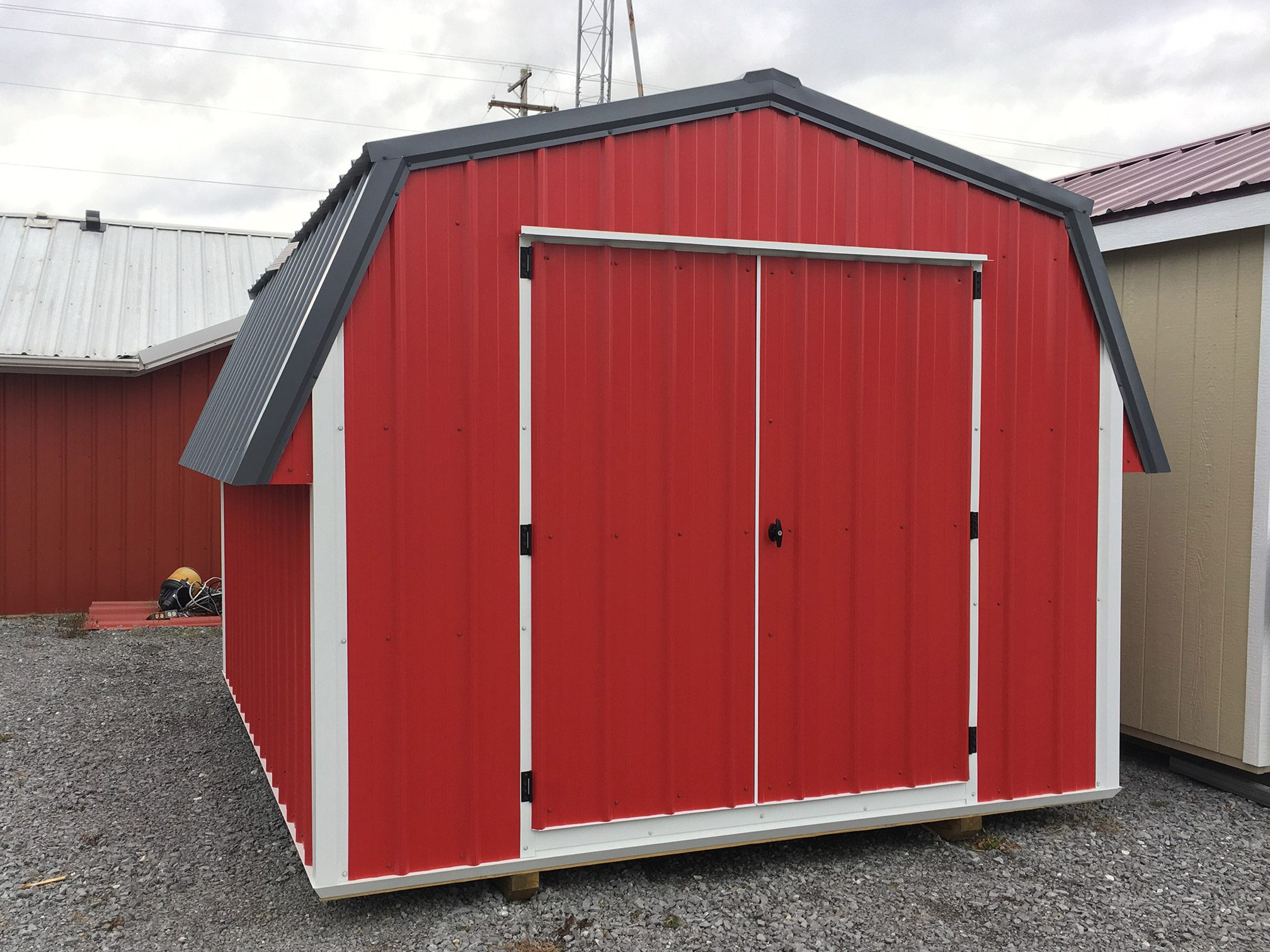 Red, White, and Black short metal building roughly 10x12